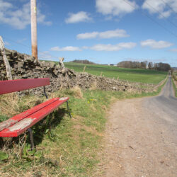 Photograph of red bench on the back road (C11) just outside Stow.