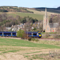 ScotRail train passing Stow with St Mary's of Wedale in the background